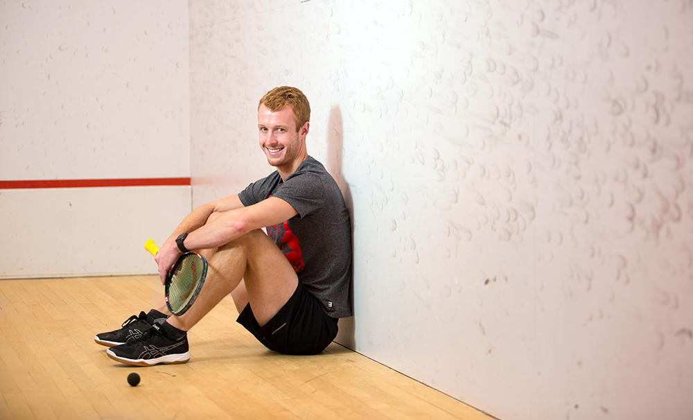 Andrew Schnell sitting down in a squash court